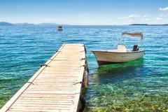 站立在木码头的空的小船在明亮的阳光下 图库摄影