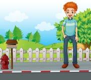 站立在木邮箱附近的一个微笑的人 免版税库存图片
