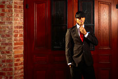 站立在木门前面的衣服的人修理领带 免版税图库摄影