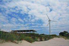 站立在未完成的大厦附近的风轮机的明亮的图片 库存照片