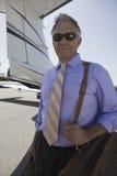 站立在机场的愉快的资深商人 免版税图库摄影