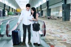 站立在机场的年轻夫妇 免版税库存照片