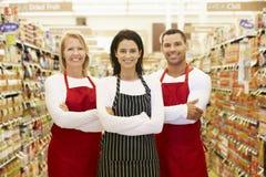站立在杂货走道的超级市场工作者 库存图片