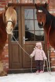 站立在村庄门附近的小女孩和两匹马 免版税图库摄影