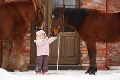 站立在村庄门附近的小女孩和两匹马 免版税库存图片