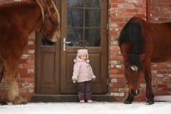 站立在村庄门附近的小女孩和两匹马 免版税库存照片