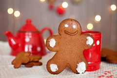 站立在杯子前面的微笑的姜饼人 茶壶和m 库存图片