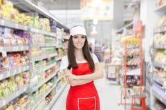 站立在架子中的微笑的超级市场雇员 免版税库存图片