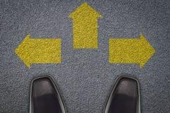 站立在柏油路的三个箭头前面的商人, 免版税库存照片