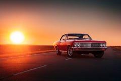 站立在柏油路的减速火箭的红色汽车在日落 库存照片