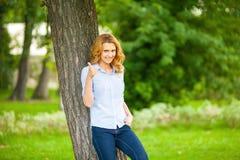 站立在树旁边的美丽的少妇 库存图片