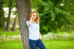 站立在树旁边的美丽的少妇 免版税库存图片