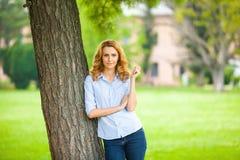 站立在树旁边的美丽的少妇 库存照片