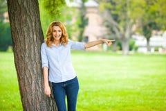 站立在树旁边的美丽的少妇 图库摄影