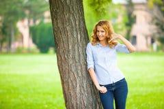 站立在树旁边的美丽的少妇 免版税图库摄影