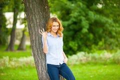 站立在树旁边的美丽的少妇 免版税库存照片