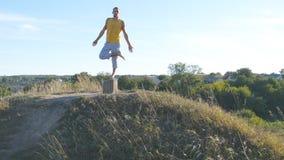 站立在树瑜伽姿势的运动的人室外 信奉瑜伽者实践的瑜伽移动并且安置本质上 平衡的运动员  免版税库存照片