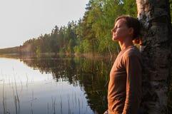 站立在树的少妇享受日落的平安的片刻与反射的在湖水 免版税库存图片