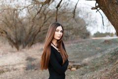 站立在树附近的时髦的女孩在早期的春天 免版税库存图片