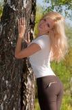 站立在树附近的妇女 免版税库存照片