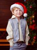 站立在树da前面的圣诞老人帽子的滑稽的男孩 免版税图库摄影
