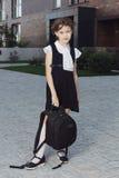 站立在校园里的制服的逗人喜爱的基本的女小学生 库存图片