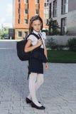 站立在校园里的制服的逗人喜爱的女小学生 免版税库存照片