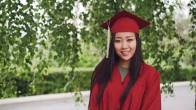 站立在校园里的可爱的亚裔褂子的女孩成功的研究生和灰泥板画象,微笑和 股票录像