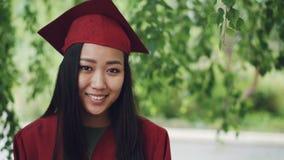 站立在校园里的可爱的亚裔褂子的女孩研究生和灰泥板慢动作画象,微笑 股票视频
