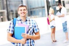 站立在校园里的愉快的学生 免版税库存照片