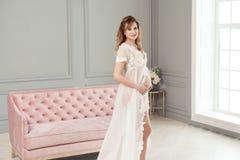 站立在桃红色沙发附近的白色礼服peignoir的怀孕的年轻女人,握充满爱她的腹部 免版税图库摄影