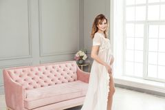 站立在桃红色沙发附近的白色礼服peignoir的怀孕的年轻女人,握充满爱她的腹部 库存照片