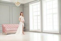 站立在桃红色沙发附近的白色peignoir的美丽的怀孕的年轻女人,握充满爱她的腹部 免版税库存照片