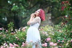 站立在桃红色玫瑰w庭院里的年轻美好的妇女ist  免版税库存图片