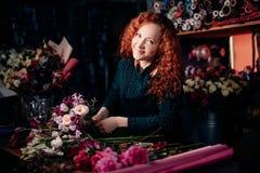 站立在桌上和做花卉构成的姜妇女在花店 库存照片