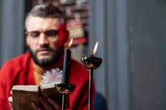 站立在桌上的两个灼烧的蜡烛在占卜者看书附近 库存照片