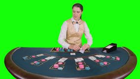 站立在桌上的赌博娱乐场女性副主持人采取从持卡者的卡片在啤牌的比赛的 绿色屏幕 慢 股票录像