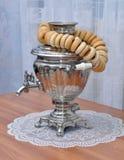 站立在桌俄国俄国式茶炊和一束百吉卷 库存图片