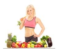 站立在桌后的妇女用水果和蔬菜 免版税库存照片