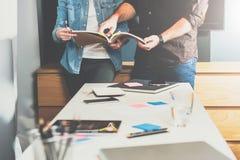 年轻站立在桌和神色上的女商人和商人在目录里 人指向在书的页 免版税库存照片