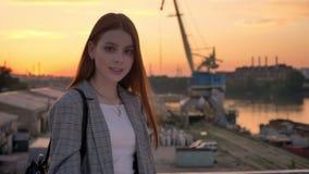 站立在桥梁和看在照相机,工业工厂背景,日落的夹克的年轻姜妇女 股票录像