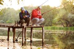 站立在桥梁的两条渔夫抓住鱼 免版税库存图片