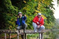 站立在桥梁的两条渔夫抓住鱼 免版税图库摄影