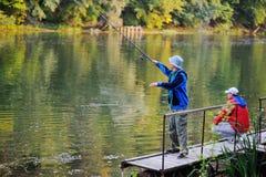站立在桥梁的两条渔夫抓住鱼 免版税库存照片
