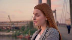 站立在桥梁的年轻姜妇女画象,然后看在照相机,微笑,日落 股票视频