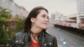 站立在桥梁的微笑的女孩接触她的看在然后附近的头发看照相机 风吹她长的头发 4K 股票视频