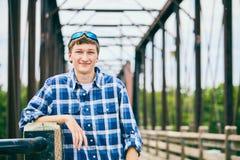 站立在桥梁的微笑的年轻人画象  库存照片