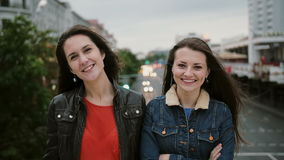 站立在桥梁,微笑,笑和看看的两个美丽的女孩照相机 风长期吹他们头发 影视素材