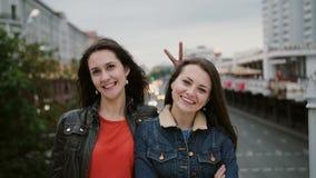 站立在桥梁,微笑,笑和看看的两个美丽的女孩照相机 风长期吹他们头发 股票录像
