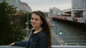 站立在桥梁,看看的美丽的女孩城市,然后转向照相机和微笑 风吹她的头发 慢的行动 股票录像